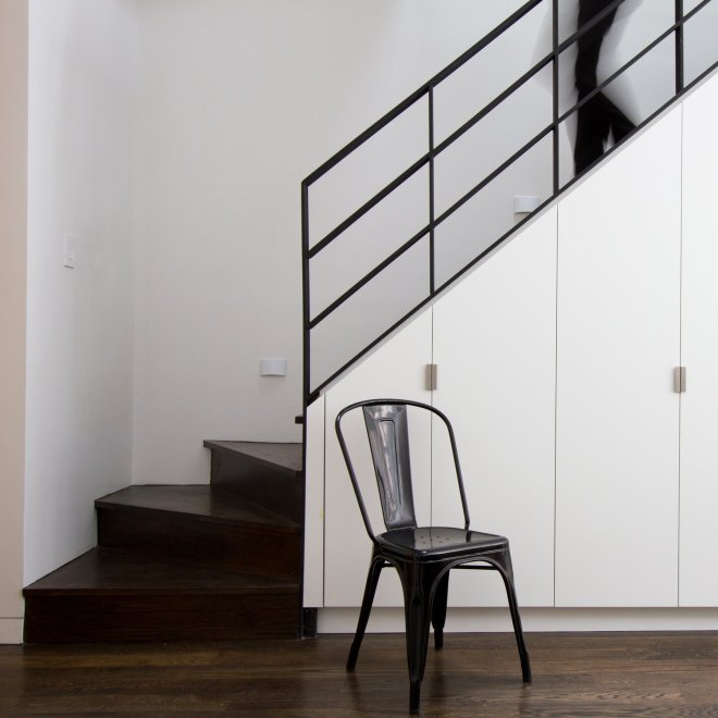 10 Smart and Surprising Under-Stair Design Solutions - Photo 4 of 10 - In a Brooklyn home renovated by Office of Architecture, subtle details on bright white cabinets keep this space under the stairs from feeling anything but dark and dreary, despite the dark wood treads and risers and black iron handrail. Thoughtful details, like simple, geometric hardware and hidden hinges, keep this often-awkward space useful and appealing.