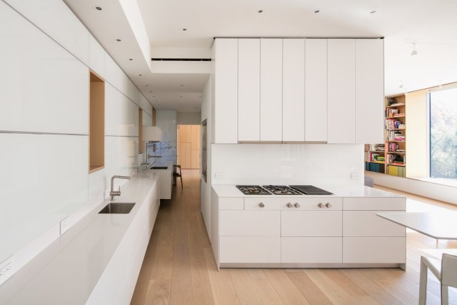 These 30 White Kitchens Are Anything But Ordinary - Photo 1 of 30 - A cooktop and refrigerator from Gaggenau, Bulthaup cabinets, a Miele oven, and an Asko dishwasher outfit the all-white kitchen, which is located on the entry-level floor.