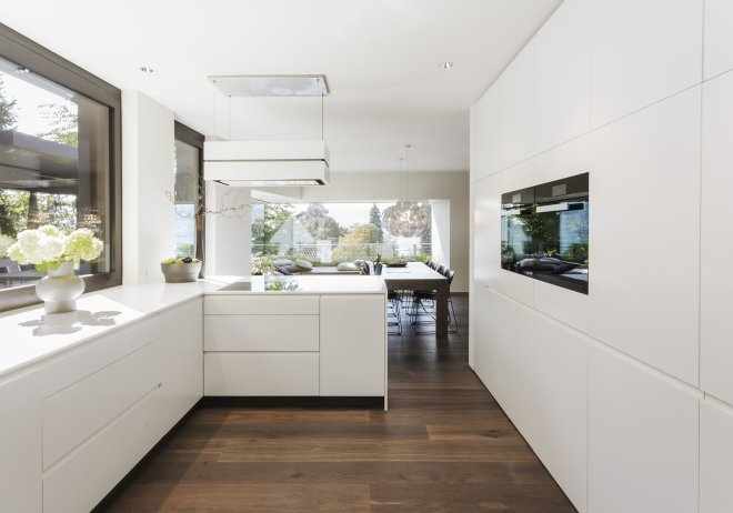 These 30 White Kitchens Are Anything But Ordinary - Photo 8 of 30 - The all-white kitchen has an L-shaped work area and  several cupboards. The work surfaces and cabinets are made of Corian, which gives the kitchen a soft elegance that blends beautifully with the oak parquet and the black steel wall. The highlight is the corner window seat.