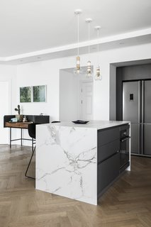 Kitchen, Refrigerator, Medium Hardwood Floor, Wall Oven, Ceiling Lighting, Quartzite Counter, and Pendant Lighting This apartment, overlooking the beautiful beach and the urban views of Tel Aviv, was built in the late 1990s and hadn't been renovated since, until designer Maya Sheinberger came in. The kitchen cabinets were chosen in a grey color with a matte finish and for the countertops, the designer chose a bright Dekton with marble texture. Above the kitchen island, which is used for cooking and for light family meals, are three wooden lighting fixtures by Israeli designer Ohad Benit.