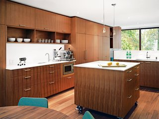 Kitchen, Dark Hardwood, Wood Cabinet, Marble Counter, and Pendant Lighting A movable island, set on stainless steel casters, sits in the center of the kitchen. The Panasonic microwave is built into the cabinetry and the August pendant lights illuminating the island are by Uberhaus.