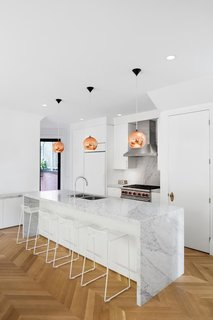 "Kitchen, Range Hood, Marble Counter, Pendant Lighting, Range, White Cabinet, Undermount Sink, Medium Hardwood Floor, Marble Backsplashe, and Recessed Lighting The renovation of a 2,000-square-foot property updates a century-old design for a family of four. ""We placed the kitchen at the center of the house to link with the dining room and the outdoor space,"" Moreau says. In the kitchen, a Wolf oven brings out the silver details in Coit's Bianco Cararra backsplash and island. Hee bar stools by Hay are lined under the island."