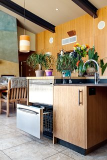 Kitchen, Ceiling Lighting, and Pendant Lighting A barrier-free house enables a family to come together amid the vineyards in Northern California. The kitchen is fully accessible and yet not institutional, with room for both extended family and a caregiver, and the ability to move between indoors and out without having to negotiate a single barrier. The island contains a micro kitchen for the family's daughter, who is in a wheelchair, with a sink, refrigerator, and warming drawers within easy reach. The pendant is from Global Lighting.