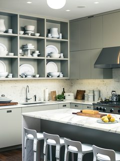 "Kitchen, Marble Counter, Marble Backsplashe, Range Hood, Range, and Open Cabinet Custom kitchen cabinets designed by Pulltab and fabricated by Maciek Winiarczyk hold mostly vintage ironstone that Geiger has found at flea markets and estate sales over the past 20 years. ""I love white,"" she says, ""because I think food always looks better on it."" She also collects vintage wooden cutting boards, shown resting against the marble tile backsplash from Stone Source."