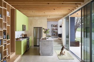 "Kitchen, Concrete Floor, Refrigerator, and Colorful Cabinet Guess used inexpensive graded pine plywood so that he would get heavy grain patterns on the surfaces. One of the main goals in the kitchen was simplicity. To that end, he opted for a poured-in-place concrete island. ""We didn't know if we could afford to do that, but we found a great subcontractor [Nate Francis of Countertop Creations] here who had never really built anything like that,"" Guess says. ""Because he was interested in giving it a shot and adding it to his portfolio, he didn't charge an exorbitant amount of money because it was sort of an experiment for him as well."" The kitchen features a GE Profile refrigerator and KitchenAid range, microwave, and dishwasher. The sink and faucet are from Kohler. The project's builder was Joe Doherty with Custom Homecrafters of Austin."