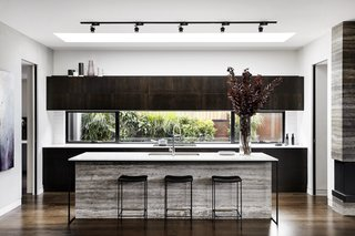 Kitchen In this kitchen in Australia, a freestanding island is lit by a skylight and track lighting, while the texture and color of the siding of the island provide a marked contrast to the dark cabinetry of the rest of the kitchen. An oversized sink makes the island an ideal prep space.