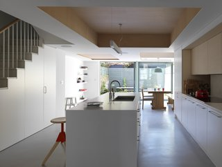 Kitchen At this home renovation in England, the architects kept the interiors minimal and stripped back, allowing for extra space to be used by the family as they pleased. A kitchen island with exposed plywood on the interior but painted on the exterior doubles up as a breakfast bar, and holds storage space for three Magis swivel beech barstools to be tucked away when not in use.