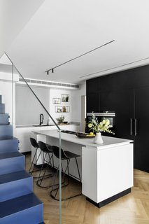 Kitchen In an apartment renovation in Tel Aviv by Maya Sheinberger, a white and black kitchen comes together in a white island with black base and black bar stools by infiniti.