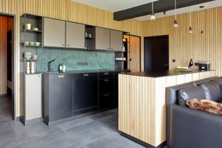 Kitchen, Laminate, Ceramic Tile Floor, Marble Backsplashe, and Pendant Lighting In a mountain retreat in the Czech Republic near the border with Germany, Martina Schultes designed a kitchen that brings the outside in, with wood plank paneling used on the walls and the kitchen island. The island and countertops are topped with black laminate, and the backsplash is a green marble.
