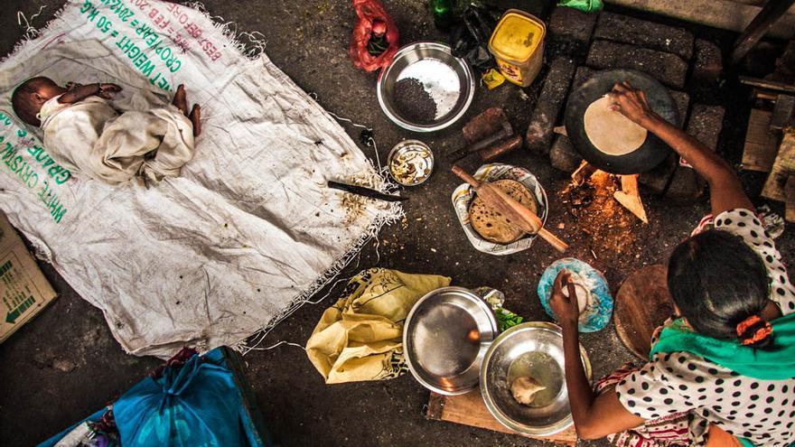 Una mujer prepara comida junto a las vías del tren en un slum de Varanasi, India. Octubre de 203 (Foto: Juan Luis Sánchez)