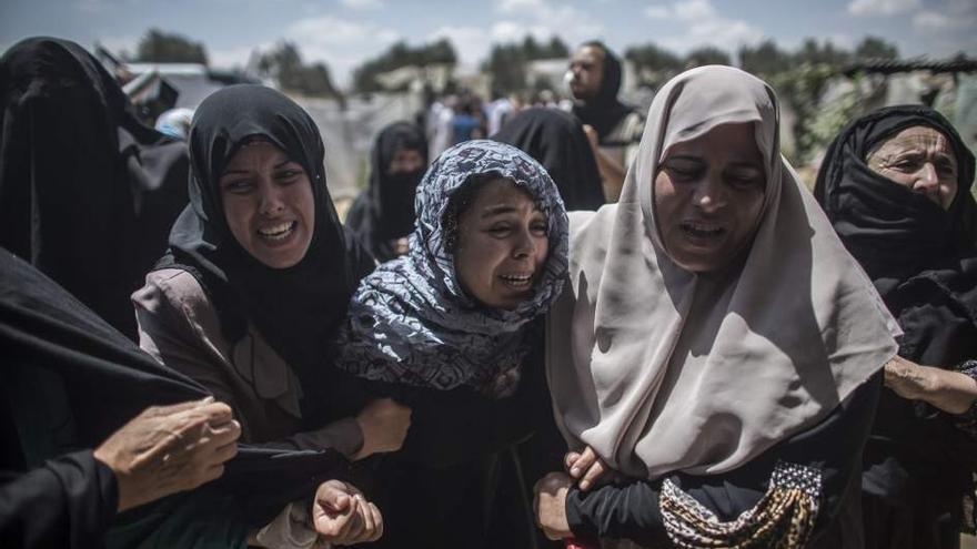 Mujeres palestinas de Gaza lloran por la muerte de varios integrantes de una familia, entre ellos niños (Efe)