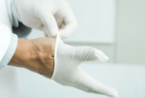 A doctor putting on latex gloves.