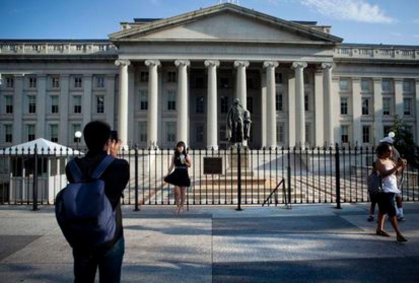 Un turista posa frente al edificio del Departamento del Tesoro en Washington DC.