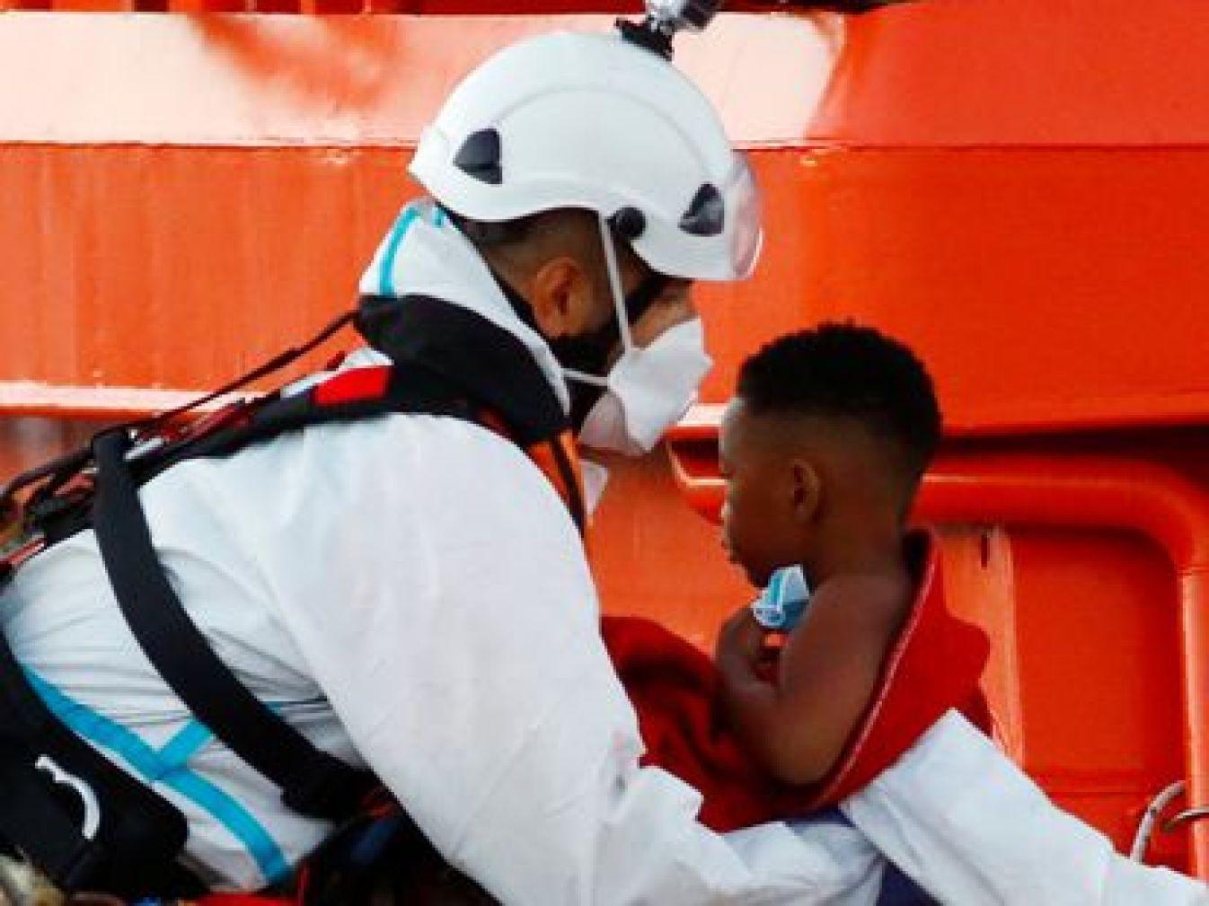Un niño migrante es recogido por un barco de la Guardia Costera española en el puerto de Arguineguín en la isla de Gran Canaria.