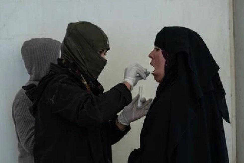 Un miembro de las SDF recolecta muestras de ADN de una mujer en la División Nacional Iraquí en el campamento de Al-Hol.