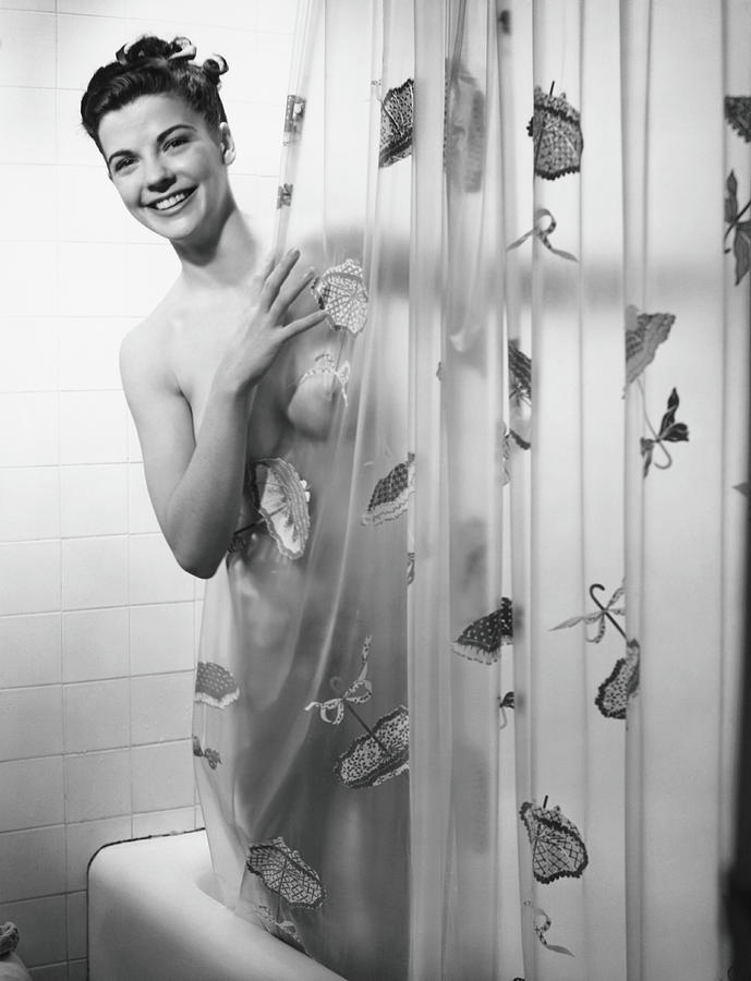 woman peering through shower curtain by george marks