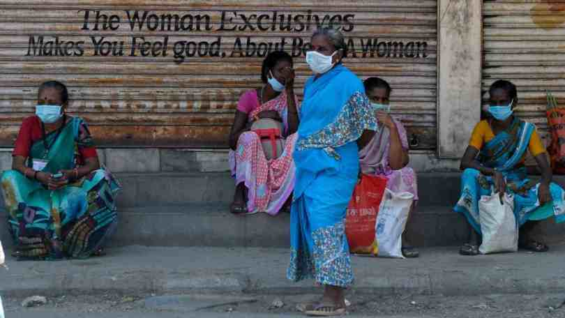 Women wearing facemasks sit in front closed shops during a government-imposed nationwide lockdown. Image: AFP Photo