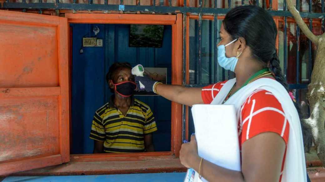 Health worker checks the body temperature of a man in Chennai. In April, a 16,000-person surveillance team, mostly women, went door-to-door with minimal personal protective equipment to find people infected with Covid-19. Image credit: Arun Sankar/AFP