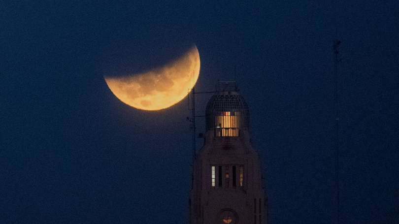 The moon sets behind the Montevideo port, in Uruguay. For a small period of time, the eclipse was visible from the northeastern parts of India (except Sikkim), some parts of West Bengal, some coastal parts of Odisha and Andaman and the Nicobar Islands. Image credit: AP Photo/Matilde Campodonico