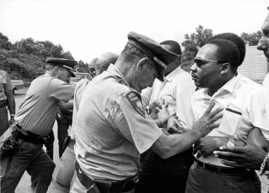 Martin Luther King Jr. being shoved back by Mississippi police during march