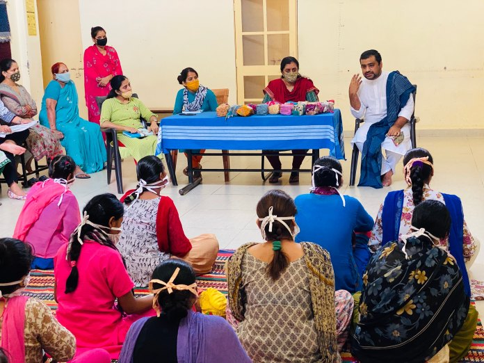 Anurag Chauhan (in white on stage) during a workshop on menstrual hygiene in a rural area. (HT Photo)