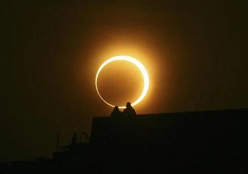 """वलयाकार सूर्य ग्रहण देखने के लिए पुल पर बैठे दो आदमी -- a . के साथ """"आग की अंघूटी"""" झेंग्झौ, हेनान प्रांत में, जनवरी १५, २०१०। (फाइल फोटो / रॉयटर्स)"""