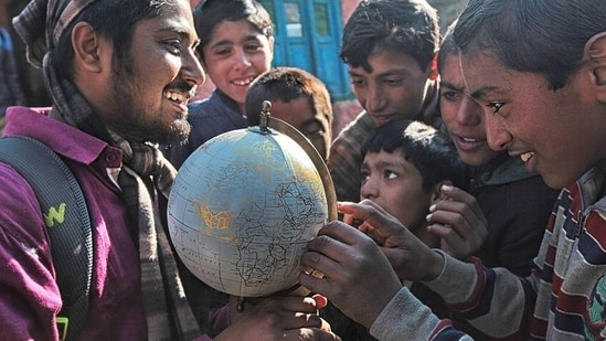 Kashmir: Close to the Line of Control between India and Pakistan, a group of Kashmiri children try to spot their village on a globe gifted to their school by a visiting NGO.(Photo: Vijay S Jodha )