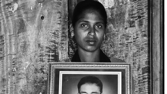 V Mary holds up an image of her late father, Anthony Swamy. This is from the award-winning First Witnesses series that uses the frame-within-a-frame to memorialise Indian farmers who have died by suicide, and their loved ones.(Photo: Vijay S Jodha )