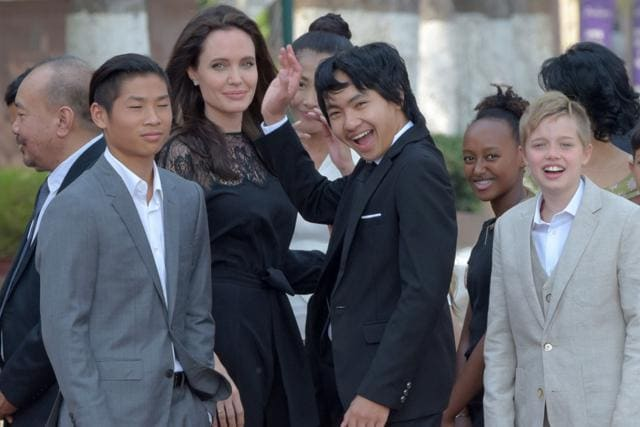 This file photo taken on February 17, 2017 shows Hollywood star Angelina Jolie (3rd L) and her children including Maddox Jolie-Pitt (C)as they gesture to media in front of the royal residence for a meeting with Cambodian King Norodom Sihamoni in Siem Reap.(AFP)