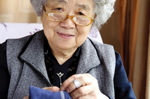 Asian woman is an Elderly Orphan living alone but with a plan for future care needs. She's an example of how to prepare for aging stages.