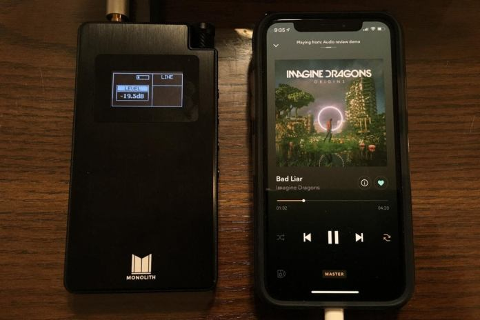 The Monolith portable headphone amplifier connected to an iPhone XS. The two are comparable in size.