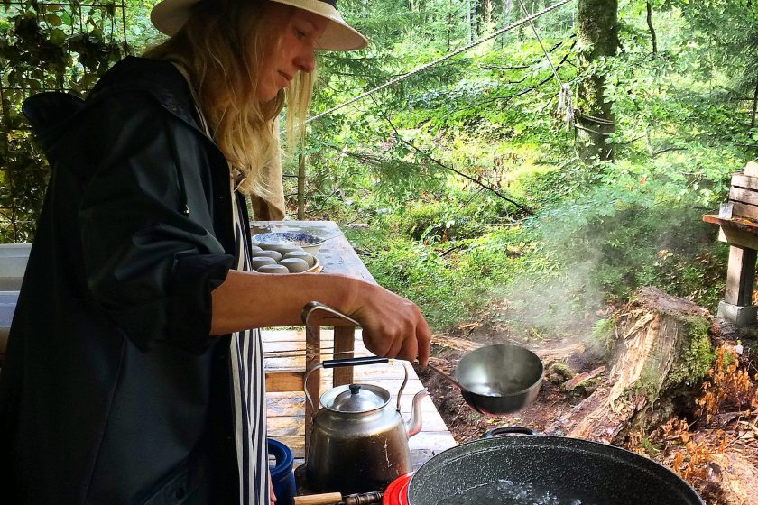 Lady ladling water out of a pot in the middle of the forest