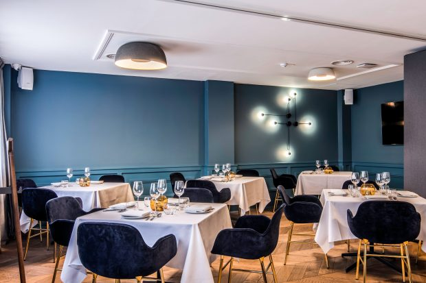 A room with sea-blue-painted walls is dotted with tables for four. They have velvet dark blue armchairs and white linen on the tables. There is parquet flooring on the floor