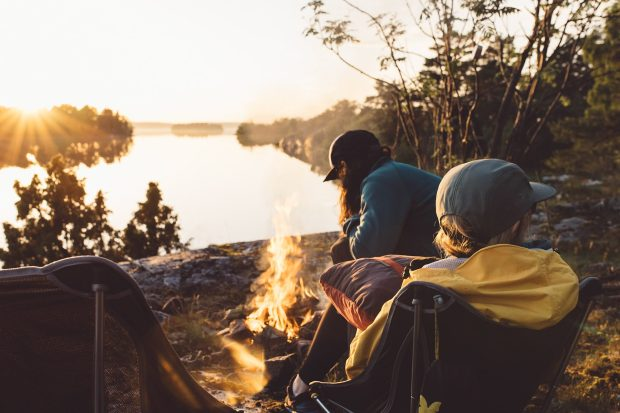 People are sat around a campfire as the sun sets over a lake in Sweden