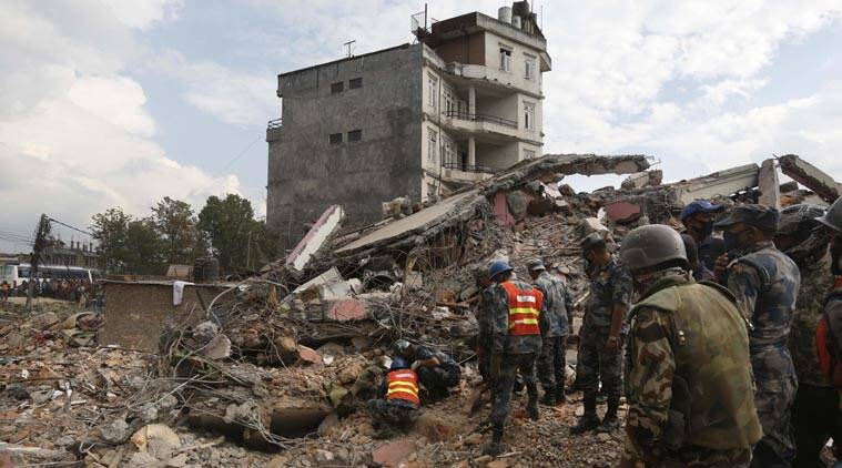 Nepalese policemen look for survivors in the debris of a building that collapsed in an earthquake in Kathmandu, Nepal ,Sunday, April 26, 2015. Sleeping in the streets and shell-shocked, Nepalese cremated the dead and dug through rubble for the missing Sunday, a day after a massive Himalayan earthquake devastated the region and destroyed homes and infrastructure. (AP Photo/Manish Swarup)