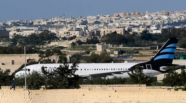 An Afriqiyah Airways plane from Libya stands on the tarmac at Malta's Luqa International airport, Friday, Dec. 23, 2016. Two hijackers diverted a Libyan commercial plane to Malta on Friday and threatened to blow it up with hand grenades, Maltese authorities and state media said. (AP Photo/Jonathan Borg)