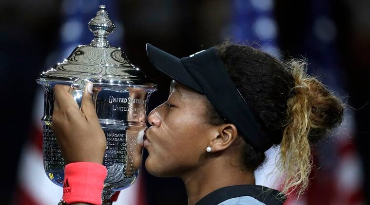 Naomi Osaka, of Japan, kisses the trophy after defeating Serena Williams in the women's final of the U.S. Open tennis tournament