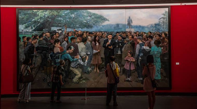 Visitors look at a painting of Xi Jinping