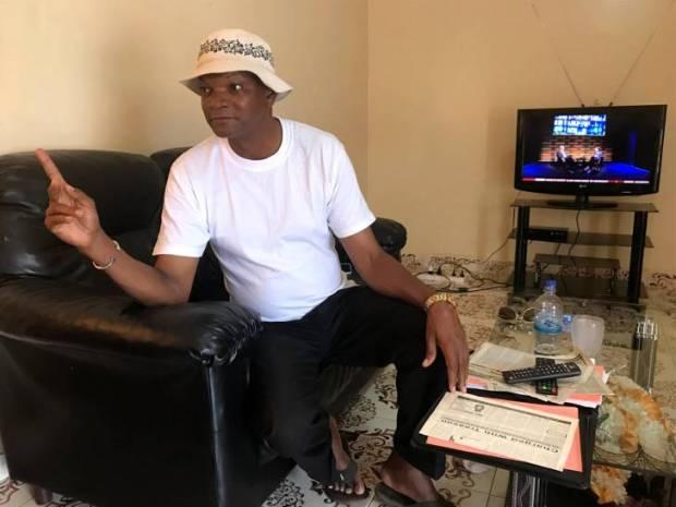 Batch Samba Jallow, assis dans un fauteuil de sa maison de Banjul, raconte à JusticeInfo comment il a été torturé en 1995 sous le régime de Yahya Jammeh.