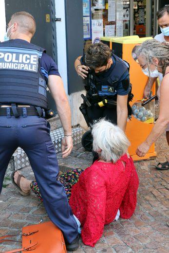 Françoise Fontanier en train de se relever, entourée des deux agents de la police municipale.