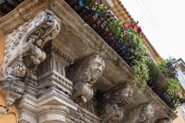 Balcony with iron railing with marble capitals and friezes baroque. Syracuse, Sicily, Italy