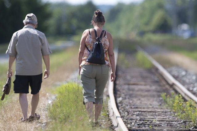 Deux personnes se recueillent près du chemin de... (Photo Jacques Boissinot, La Presse Canadienne)
