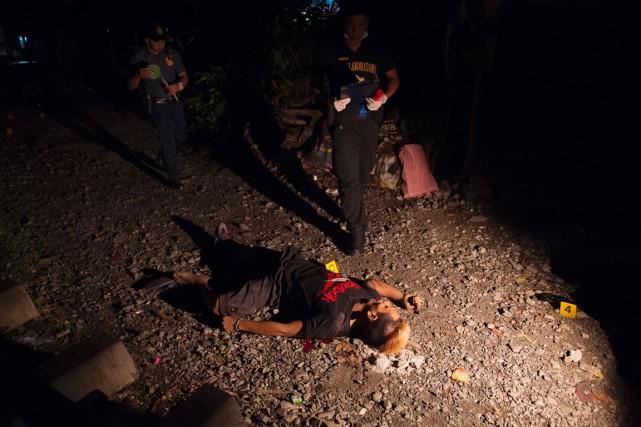 Des policiers cherchent des indices sur la scène... (photo TED ALJIBE, AFP)