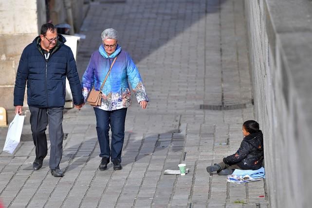 Sur cette photo, des piétons passent devant un... (PHOTO LOIC VENANCE, ARCHIVES AFP)