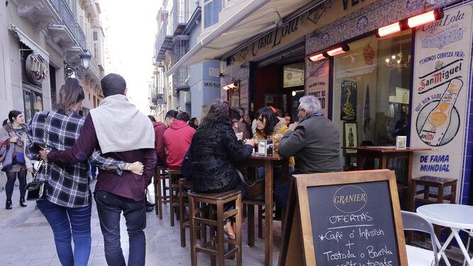 Una pareja pasa junto a la terraza de un bar del Centro de Málaga.