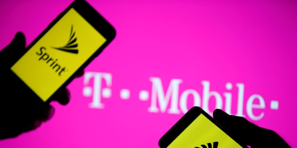 A smartphones with Sprint logo are seen in front of a screen projection of T-mobile logo, in this picture illustration taken April 30, 2018. REUTERS/Dado Ruvic/Illustration