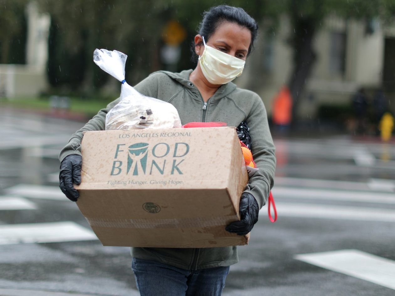 A woman carries away fresh food at a Los Angeles Regional Food Bank giveaway of 2,000 boxes of groceries, as the spread of the coronavirus disease (COVID-19) continues, in Los Angeles, California, U.S., April 9, 2020. REUTERS/Lucy Nicholson