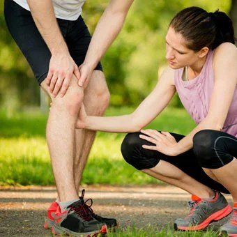 A female runner helps a male runner experiencing knee pain.