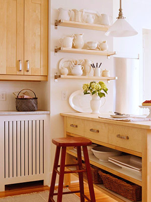 Open shelves on wall at end of peninsula hold white serving pieces