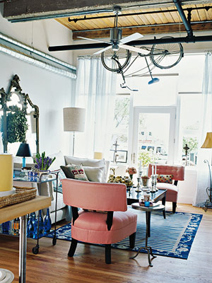 eclectic living room with pink chair and hanging bicycle